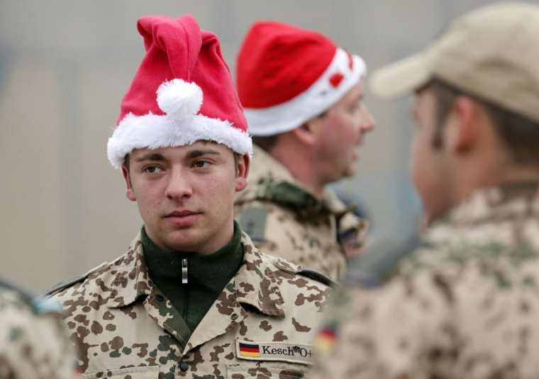 German Bundeswehr army soldiers wear Santa Claus hats in a Christmas market at their combat outpost OP North, near Baghlan, northern Afghanistan on December 9, 2012. The soldiers are celebrating their last Christmas at the combat outpost this year before it is removed in 2013. (Fabrizio Bensch/Reuters)