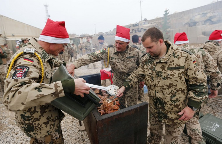 German Bundeswehr army soldiers prepare a barbecue during a Christmas market at their combat outpost OP North, near Baghlan, northern Afghanistan on December 9, 2012. The soldiers are celebrating their last Christmas at the combat outpost this year before it is removed in 2013. (Fabrizio Bensch/Reuters)