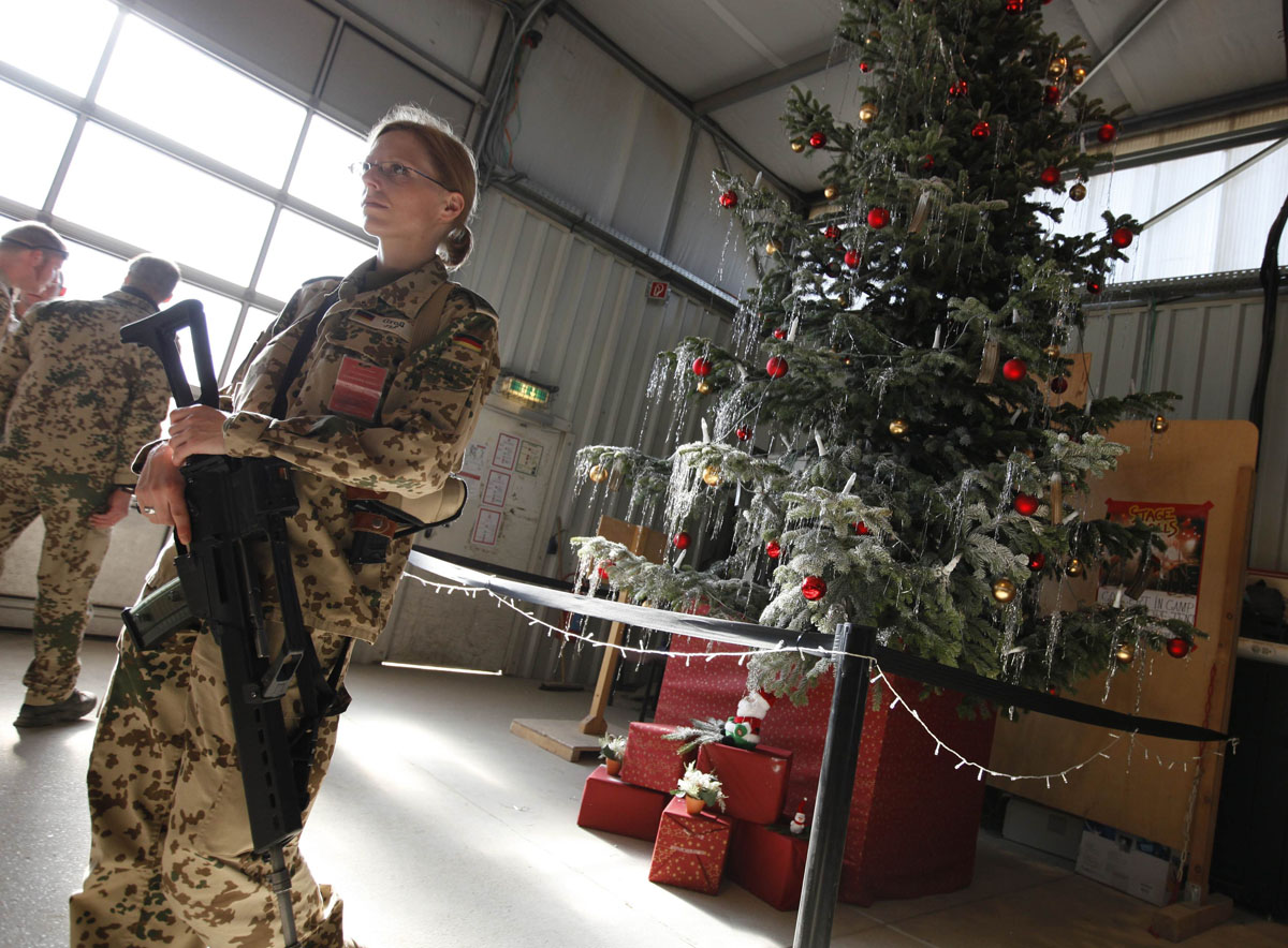 German soldier stands next to a Christmas tree at army camp