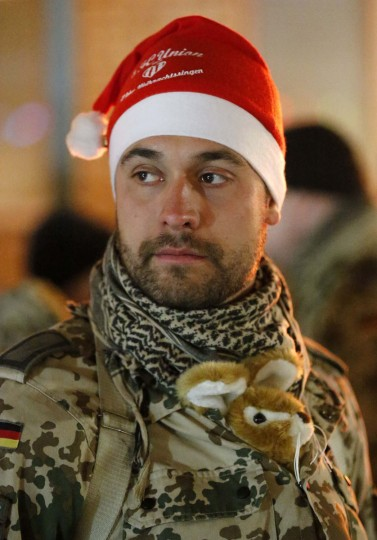 A German Bundeswehr armed forces soldier wears a Santa Claus hat during a Christmas market at camp Marmal near Mazar-e-Sharif, northern Afghanistan on December 16, 2012. (Fabrizio Bensch/Reuters)