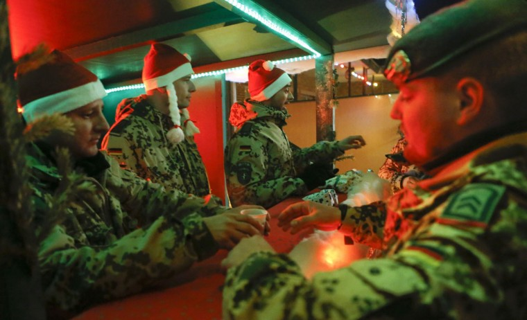 German Bundeswehr armed forces soldiers offer hot drinks at a booth during a Christmas market at camp Marmal near Mazar-e-Sharif, northern Afghanistan on December 16, 2012. (Fabrizio Bensch/Reuters)