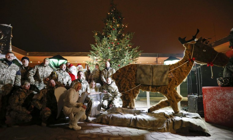 German Bundeswehr armed forces soldiers pose with comrades dressed as Santa Claus and angels during a Christmas market at camp Marmal near Mazar-e-Sharif, northern Afghanistan on December 16, 2012. (Fabrizio Bensch/Reuters)