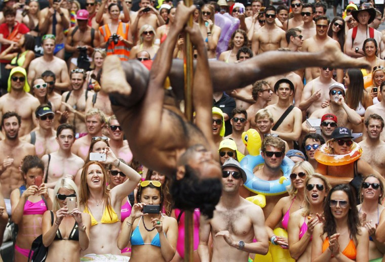 Participants of 'Strut the Streets,' an annual swimwear parade, look at a man pole dancing in central Sydney. 'Strut the Streets' raises money to help aboriginal Australians to finish school at the same rate as every Australian child. (Daniel Munoz/Reuters)