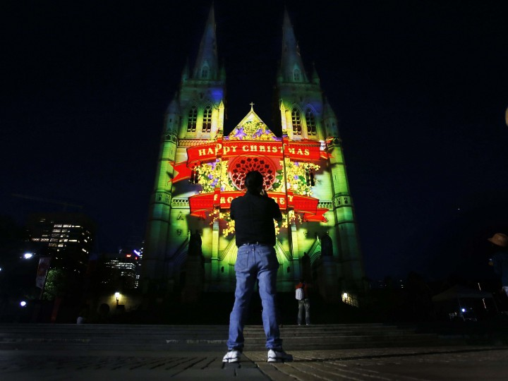 "A man photographs St Mary'­s Cathedral in Sydney as it is illuminated by a 75-metre-high (246 feet) projected display titled ""Lights of Christmas."" Organizers of the free event at Sydney's Roman Catholic Cathedral designed the display to represent modern Australia's diversity and celebrate the 500th Anniversary of Renaissance artist Michelangelo's works that decorate the ceiling of the Sistine Chapel. (Tim Wimborne/Reuters photo)"