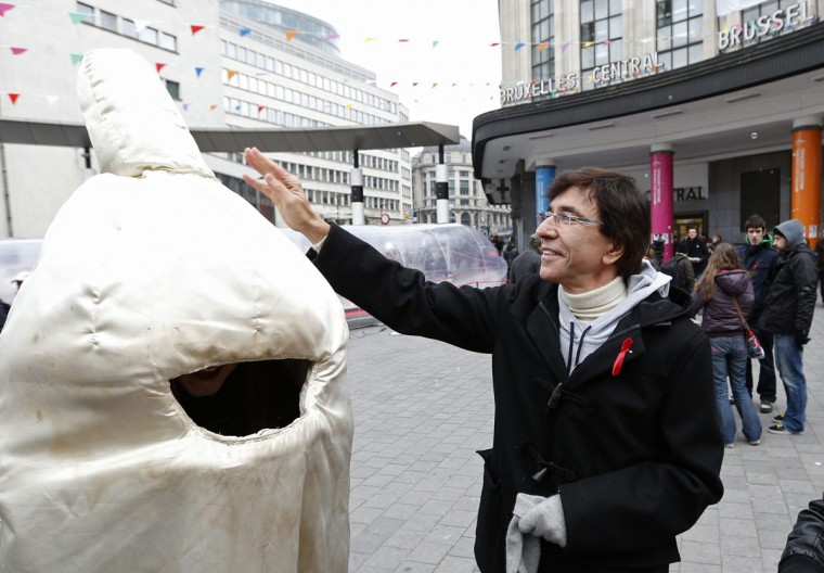 Belgium's Prime Minister Elio Di Rupo greets a volunteer dressed as a condom during an event marking World AIDS Day in central Brussels. (Francois Lenoir/Reuters)