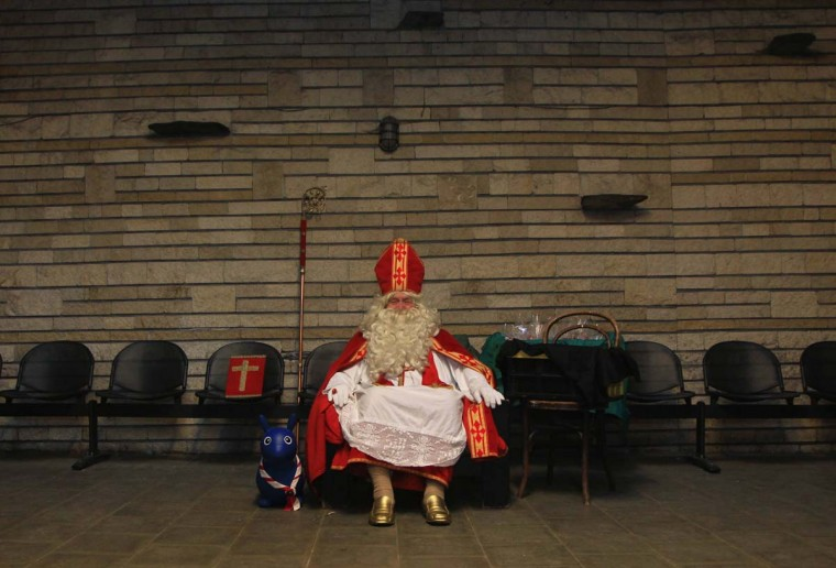 Belgian Lievin Pauwels, 72, dresses as Saint Nicholas while waiting for children at the 25th guides company in Brussels December 9, 2012. In Belgium, children traditionally wait for Saint Nicholas to bring them sweets and presents on the night of December 5. Lievin has been playing the patron saint of children for more than 40 years. (Yves Herman/Reuters)