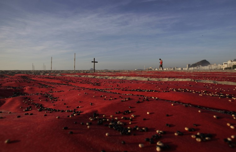 A man walks past a protest against the level of homicide in Brazil by the non-governmental group Rio de Paz in Rio de Janeiro. Some 500,000 beans were placed over red sheets by the group to represent the number of people killed over the last 10 years in Brazil, according to Rio de Paz. (Ricardo Moraes/Reuters)