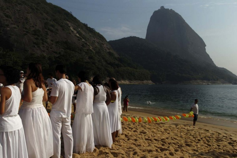 Followers of the Afro-Brazilian religion Umbanda pay tribute to Iemanja, goddess of the sea, in Praia Vermelha (Red Beach) in Rio de Janeiro December 31, 2012. Every end of the year, worshippers present gifts to the sea goddess to give thanks for the year that is finishing and ask for blessings for the upcoming new year. (Pilar Olivares/Reuters)