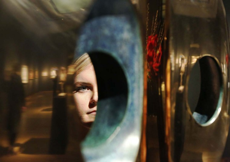 "A worker poses with Barbara Hepworth's sculpture, ""Maquette for Divided Sculpture"", at Christie's auction house in London December 10, 2012. The piece is expected to sell for 250,000 GBP (U.S. $400,000), when it is auctioned on December 18. (Luke MacGregor/Reuters)"