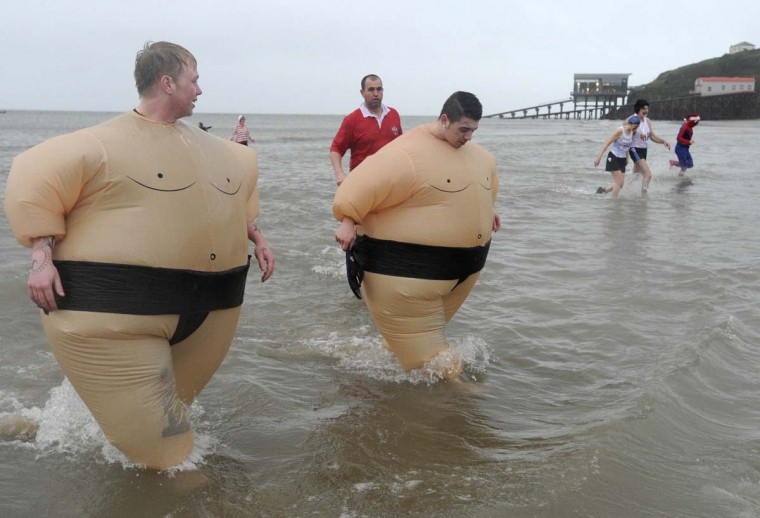 Swimmers wearing Sumo wrestler costumes take part in the annual Tenby Boxing Day swim in Tenby, Wales, December 26, 2012. (Rebecca Naden/Reuters)