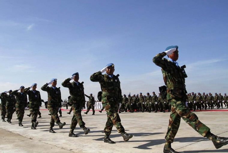 Cambodian soldiers serving with the United Nations Interim Force in Lebanon (UNIFIL) salute as they march during a send-off ceremony at Pochentong Air Base in Phnom Penh December 19, 2012. (Samrang Pring/Reuters)