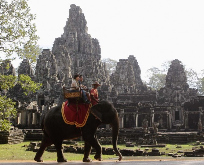 Tourists ride an elephant past the ruins of Cambodia's Bayon temple in Siem Reap December 22, 2012. Picture taken December 22, 2012. (Erik De Castro/Reuters)