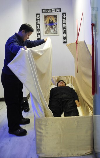 "A therapist covers a man with a piece of cloth as the man lies in a coffin at a mental health clinic in Shenyang. The clinic opened three years ago and offers patients the experience of ""death"" by having them lie in a coffin as a form of therapy. The treatment, which lasts four to five hours, costs 2000 yuan (about $320). Apart from lying in the coffin, patients also have to record their feelings on paper before and after the experience, listen to a therapist's guidance and to relatives reading ""epitaphs"". The sign on the wall reads ""experience the true meaning of life by experiencing the mystery of death"". (Sheng Li/Reuters)"