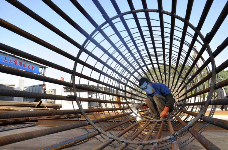 A worker welds steel bars at a construction site for a new train station in Ningbo, Zhejiang province. Annual growth in China's factory output, investment and retail sales may have gained pace in November thanks to recent pro-growth policies, a Reuters poll showed, reducing the chances for further policy support as inflation picks up. (China Daily/via Reuters)