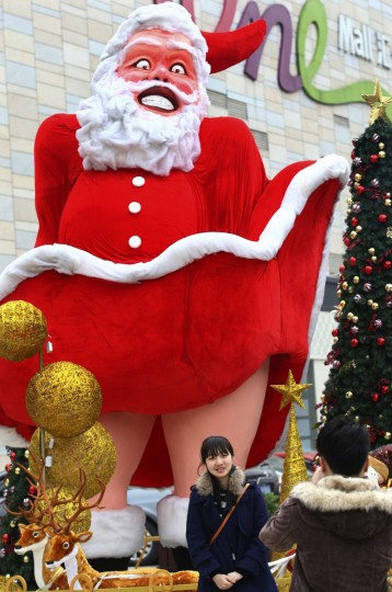 Locals take pictures in front of a Santa Claus figure outside a shopping mall ahead of Christmas in Dongguan, Guangdong province. (China Daily/via Reuters)