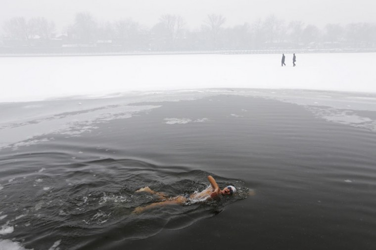 A person swims as people walk on the partially frozen Houhai Lake during winter in central Beijing. (Jason Lee/Reuters)