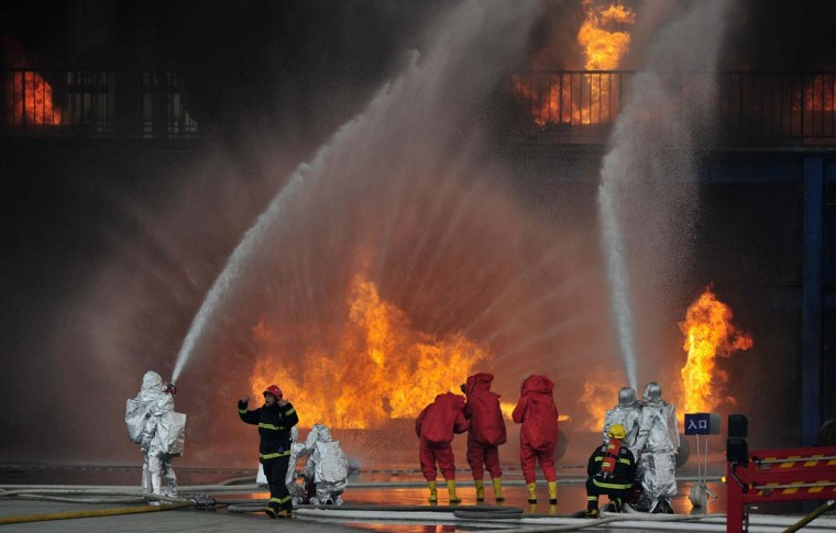 Firefighters practice during a chemical plant fire protection drill at a firefighter training base in Chongqing Municipality. At least 300 personnel and 30 fire engines participated in the exercise on Thursday. (Shi Tou/Reuters photo)