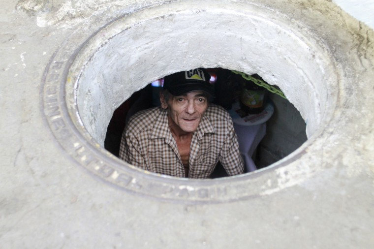 Miguel Restrepo, 62, looks up from his sewer home in Medellin. The former drug addict has been living in an abandoned sewer with his wife Maria Garcia and dog Blackie for 22 years. Their home, which is fitted with a kitchen, a fan, tv, a chair and a bed, is a 6 square meter wide and 1.4 meters high tunnel that leaks when it rains, and requires a manhole cover. (Albeiro Lopera/Reuters)
