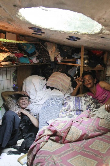 Miguel Restrepo, 62, lies with his dog in his sewer home in Medellin. (Albeiro Lopera/Reuters)
