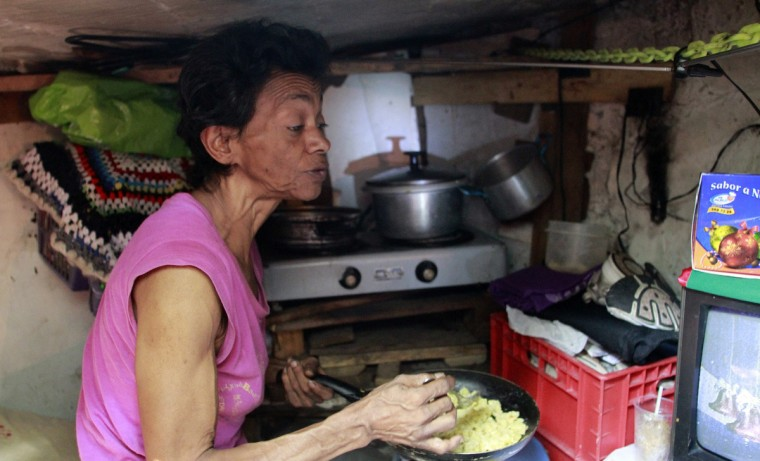 Maria Garcia cooks in the kitchen of her sewer home in Medellin. Together with her husband, Miguel Restrepo (not pictured), 62, a former drug addict, the pair has been living in an abandoned sewer with their dog Blackie for 22 years. (Albeiro Lopera/Reuters)