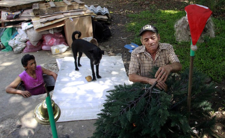 Miguel Restrepo, 62, and wife Maria Garcia (R) make Christmas ornaments outside their sewer home in Medellin. (Albeiro Lopera/Reuters)