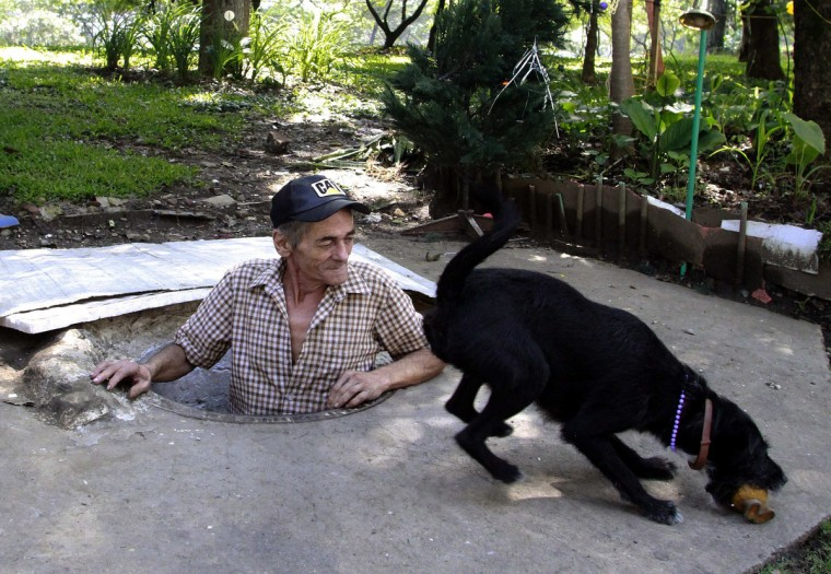 Miguel Restrepo, 62, plays with his dog Blackie at his sewer home in Medellin. (Albeiro Lopera/Reuters)