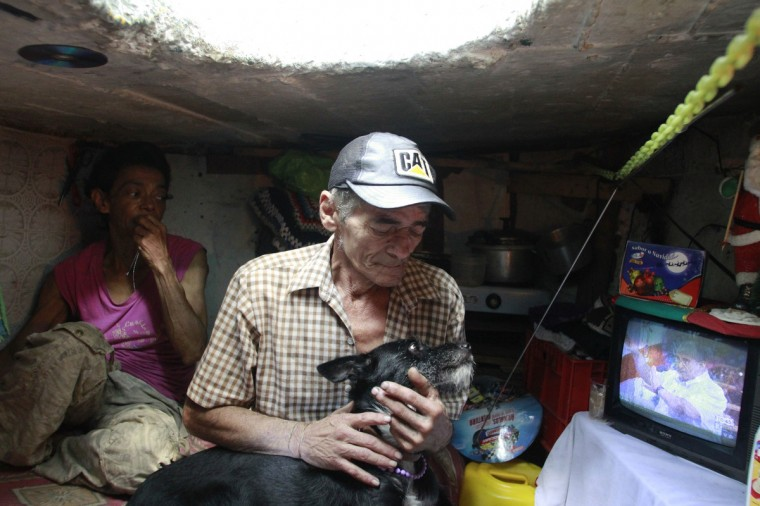 Miguel Restrepo, 62, plays with his dog Blackie in his sewer home in Medellin. (Albeiro Lopera/Reuters)