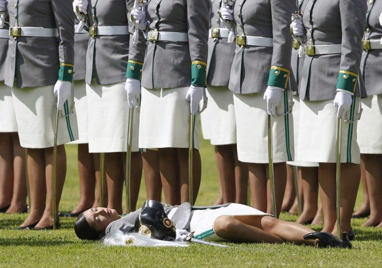 A cadet lies on the grass after collapsing during a promotion ceremony at a police school in Bogota, Colombia. (John Vizcaino/Reuters)