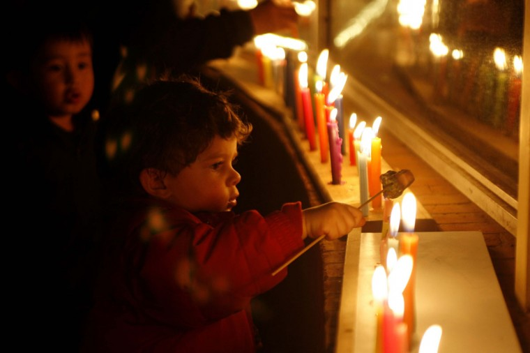 Children are seen next to candles lit to celebrate Dia de las Velitas, or Candle Day, in the neighborhood of Belen in Bogota on December 7, 2012. The candlelight event takes place every year to honor the Virgin Mary and mark the start of Christmas festivities.(Fredy Builes/Reuters)