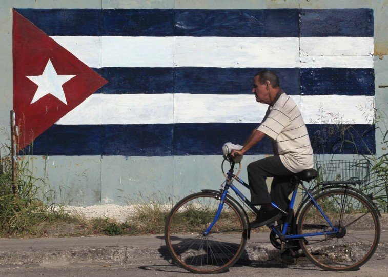 A Cuban flag is seen on a wall as a man rides his bicycle in Havana December 31, 2012. (Enrique De La Osa/Reuters)
