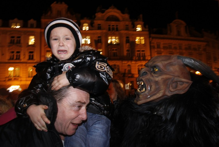 A child reacts to a reveler dressed as a devil at the Old Town Square in Prague, on the eve of Saint Nicholas Day. Revelers dressed as Saint Nicholas and a devil approached children on the streets as part of a tradition to determine if they had behaved well during the past year and depending on their answers, would receive presents, sweets or coal accordingly. (David W Cerny/Reuters)