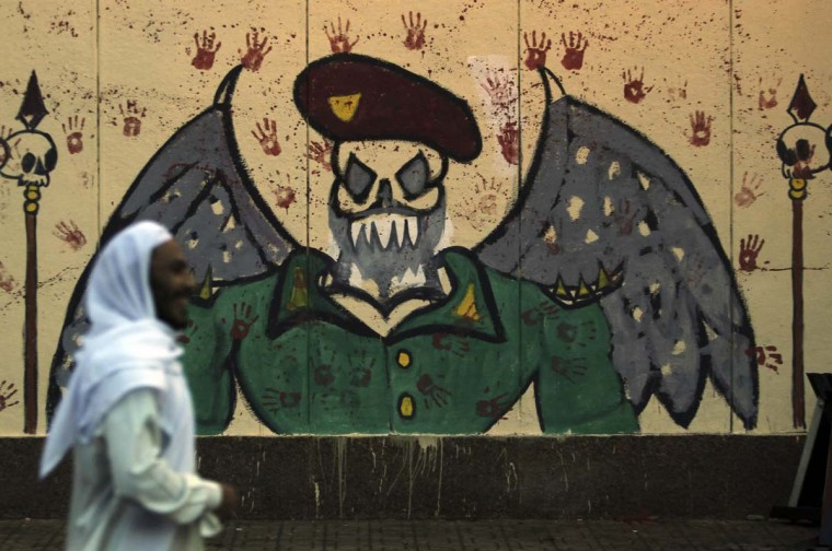 """An anti-Mursi protester walks in front of graffiti on the wall at the presidential palace in Cairo, December 8, 2012. Egypt's military, stepping into a crisis pitting Islamist President Mohamed Mursi against opponents who accuse him of grabbing excessive power, said on Saturday only dialogue could avert """"catastrophe."""" (Amr Abdallah Dalsh/Reuters)"""