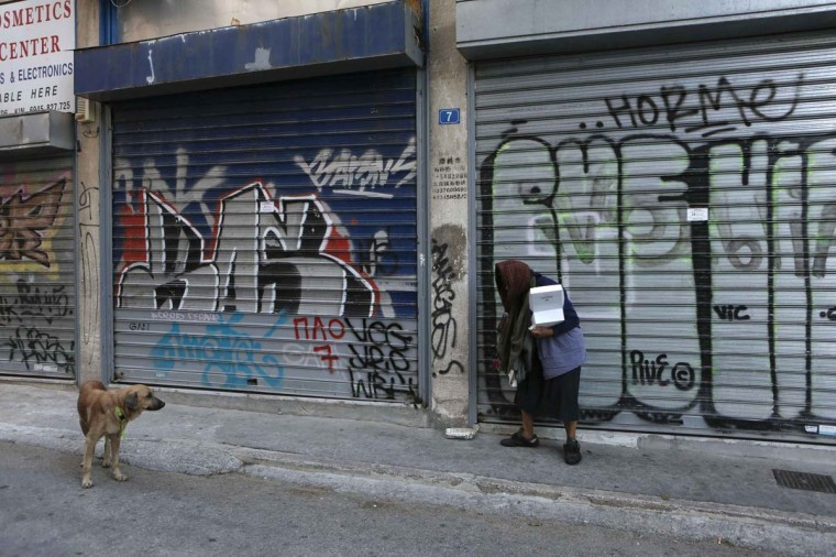 A homeless woman leaves food for a stray dog at a small street of Athens November 6, 2012. Thousands of Greek workers began a 48-hour strike on Tuesday to protest a new round of austerity cuts that unions say will devastate the poor and drive a failing economy to collapse. (Yorgos Karahalis/Reuters)