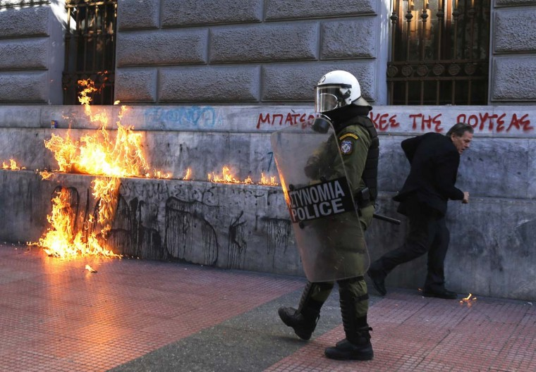 A pedestrian runs to avoid a fire caused by a petrol bomb thrown by protesters during a rally to mark the 2008 shooting of a student by police in Athens' Syntagma (Constitution) square in Greece. (Yannis Behrakis/Reuters photo)
