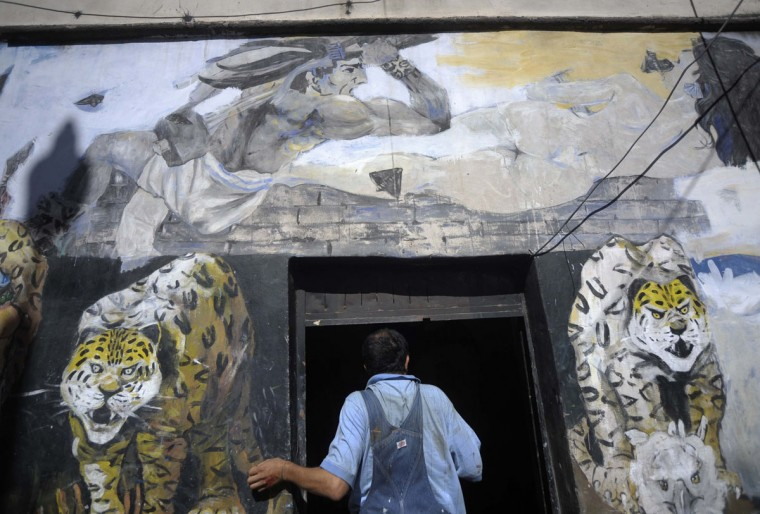 "Honduran urban artist Nelson Salgado stands in the entrance of his workshop in Tegucigalpa next to a mural named ""The Conquest"" which depicts Mayan characters. Salgado plans to paint at least 15 paintings related to the current Mayan Long Count calendar, which ends on December 21, 2012. While some think the calendar's end is a prediction of the apocalypse, researchers say the date marks the beginning of a new calendar cycle. (Jorge Cabrera/Reuters)"