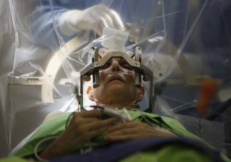 A woman lies on an operating table during a brain surgery at the National Neurology Institute in Budapest December 15, 2012. The complex operation, called deep brain stimulation (DBS) and involves stimulation of certain areas of the human brain with high-frequency electricity, is carried out with the patient awake and communicating with the doctors during certain phases of the operation. (Bernadett Szabo/Reuters)
