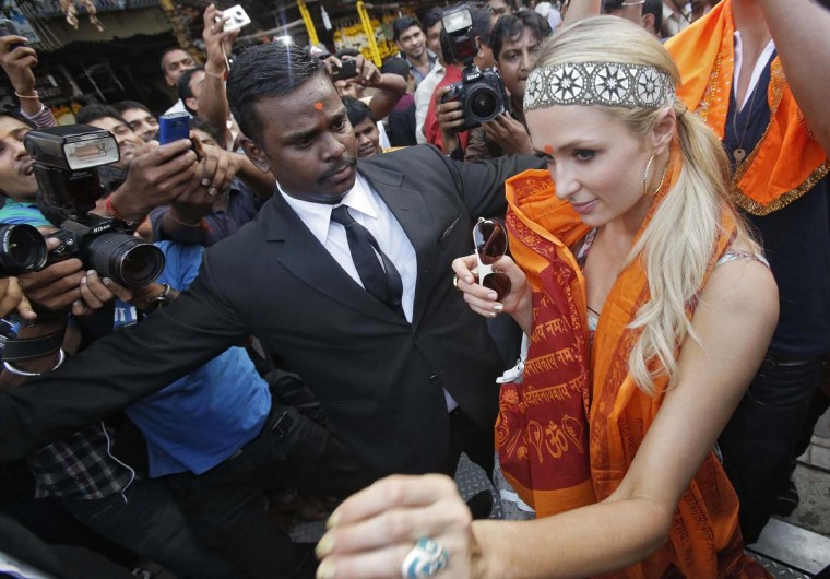 "Socialite Paris Hilton wears a ""tilak,"" the Hindu traditional mark, on her forehead and a saffron-coloured scarf as she leaves after a visit to the Siddhivinayak temple in Mumbai, December 3, 2012. Hilton is attending a fashion event as a DJ in western India. (Vivek Prakash/Reuters)"