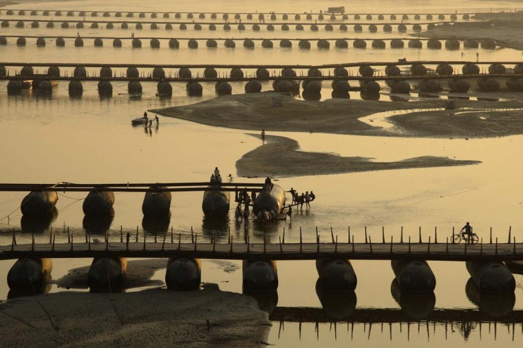 "Laborers work on an under-construction pontoon bridge spanning the river Ganga ahead of the ""Kumbh Mela"", or Pitcher Festival, as the sun sets in the northern Indian city of Allahabad December 2, 2012. (Jitendra Prakash/Reuters)"