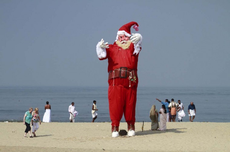 Tourists and locals walk past a Santa Claus statue placed on a beach for a film shoot in the southern Indian city of Kochi December 10, 2012. (Sivaram V/Reuters)