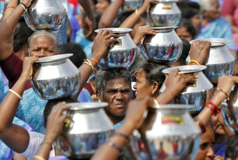 Women carry milk in aluminium pitchers to pour it into the Bay of Bengal as gesture of respect to the victims of the 2004 tsunami during the eighth anniversary of the disaster, at Marina beach in the southern Indian city of Chennai December 26, 2012. Hundreds of memorial events were held across Asia on Wednesday in memory of the towering waves that crashed ashore with little warning on December 26, 2004, killing 226,000 people in 13 countries. (Babu/Reuters)
