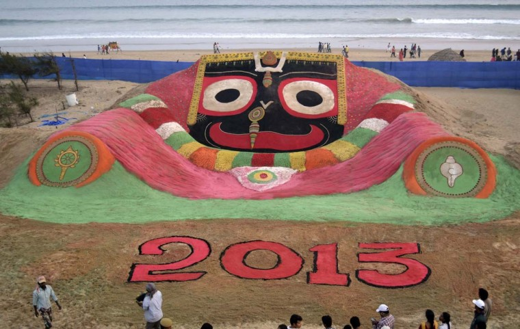 Visitors look at a sand sculpture designed to celebrate the 2013 new year by sand artist Sudarshan Pattnaik on the beach in Puri, about 40 miles from the eastern city Bhubaneswar in the Indian state of Odisha December 31, 2012. (Reuters)