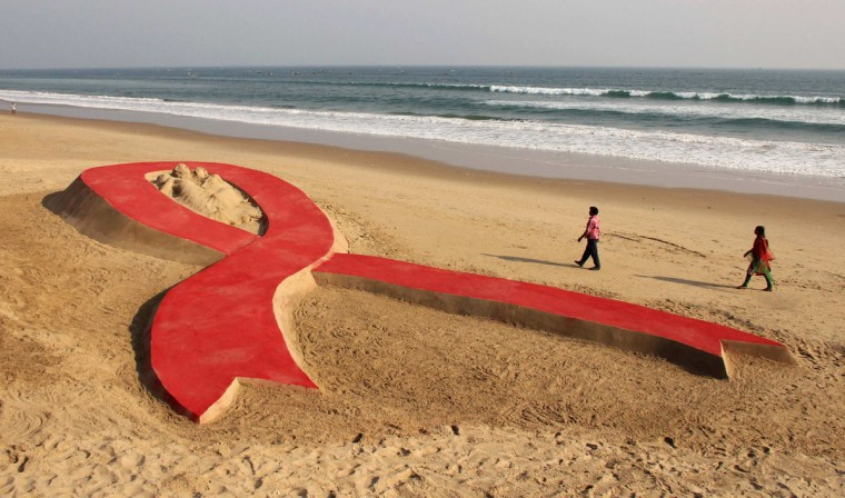 People walk near a red ribbon sand sculpture created by Indian sand artist Sudarshan Patnaik on the eve of World AIDS Day on a beach in the eastern Indian state of Odisha. (Reuters Photo)