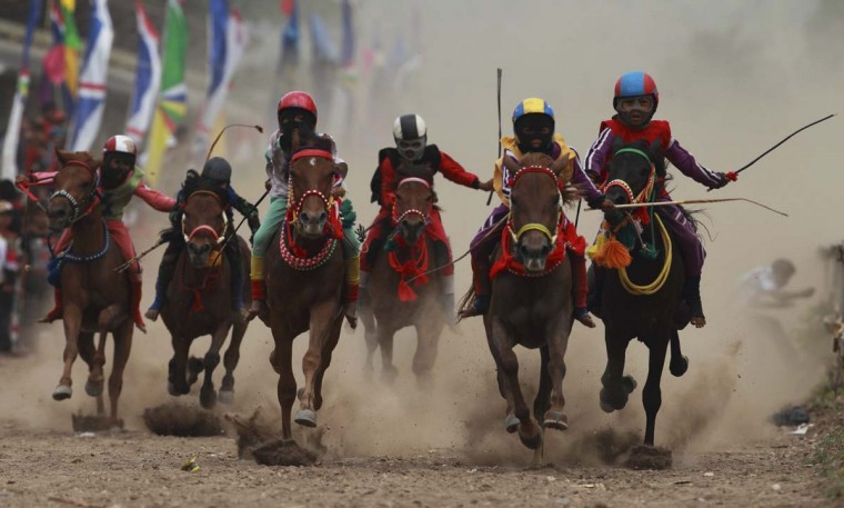 Child jockeys race their horses at a racetrack outside Bima. Dozens of child jockeys, some as young as eight-years-old take part in the races. Picture taken November 17, 2012. (Beawiharta/Reuters)