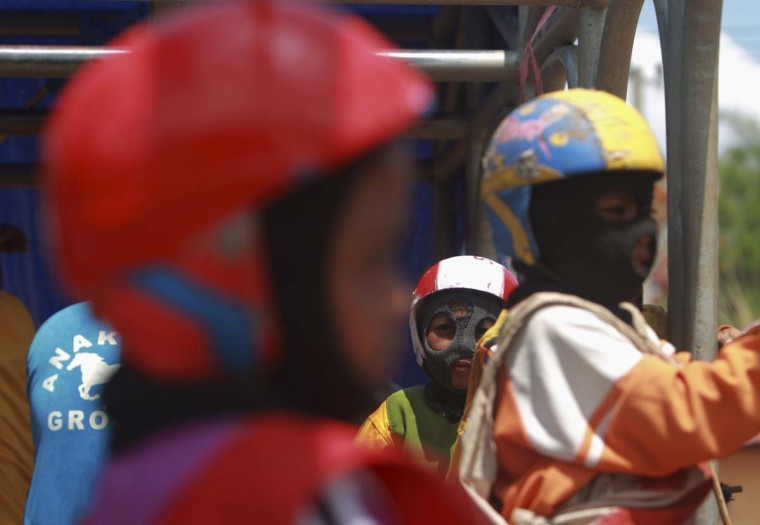 Child jockeys sit inside a starting gate before a race at a track outside Bima, November 18, 2012. (Beawiharta/Reuters)