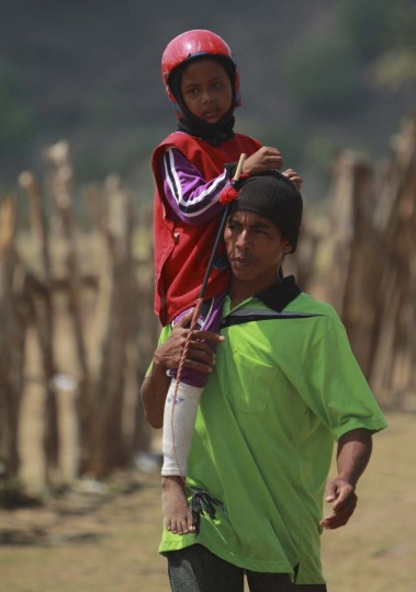 Child jockey Herman Sarifudin is held by his father Herman as walks to the starting gates before a race at a track outside Bima. Picture taken November 18, 2012. (Beawiharta/Reuters)