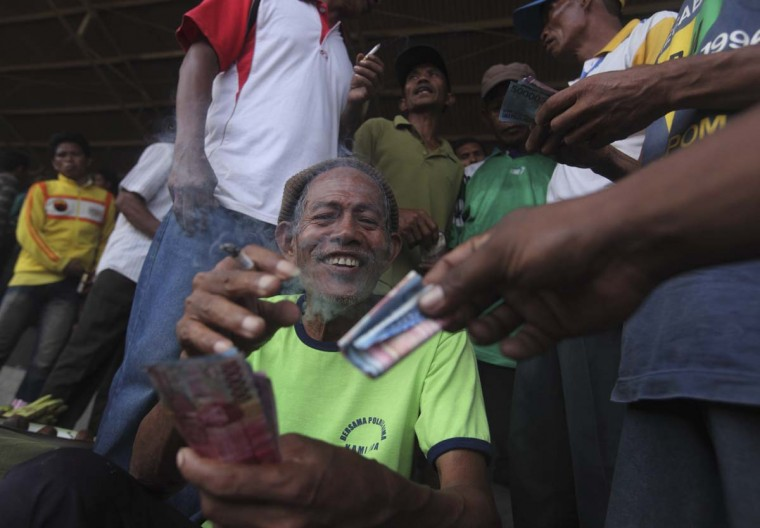 A gambler collects his money after a win on a horse race at a racetrack outside Bima. Picture taken November 17, 2012. (Beawiharta/Reuters)
