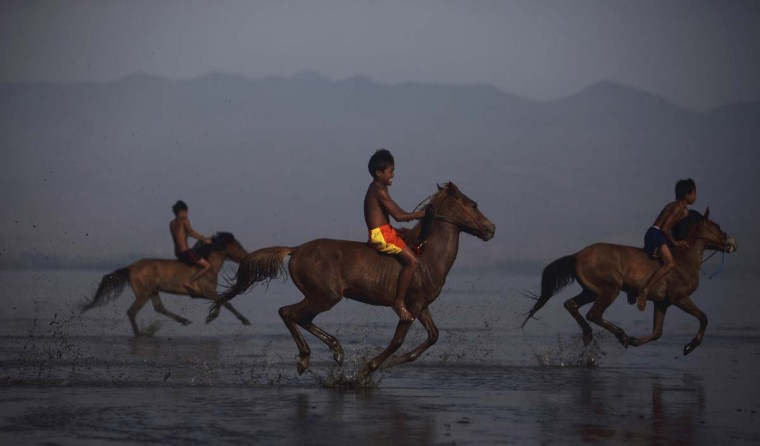 Endiansyah Mohammad (C) warms up his horse on Kalaki beach outside Bima. Dozens of child jockeys, some as young as eight-years-old take part in the races. Picture taken November 17, 2012. (Beawiharta/Reuters)