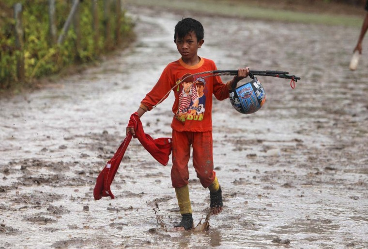 A child jockey walks on the track at Panda racecourse outside Bima. Picture taken November 17, 2012. (Beawiharta/Reuters)