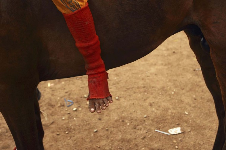 The foot of child jockey is seen as he sits on his horse at Panda racetrack outside Bima. Picture taken November 18, 2012. (Beawiharta/Reuters)