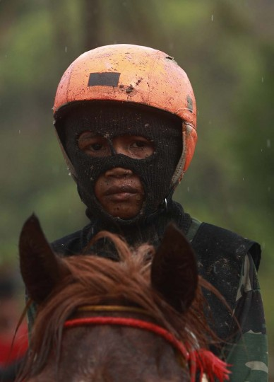 A child jockey sits on his horse after a race at Panda racetrack outside Bima. The chairman of the races' organizing team, Hajji Sukri, denies that there is any danger to the children saying they are all skilful riders and none has been killed or seriously hurt. Picture taken November 18, 2012. (Beawiharta/Reuters)
